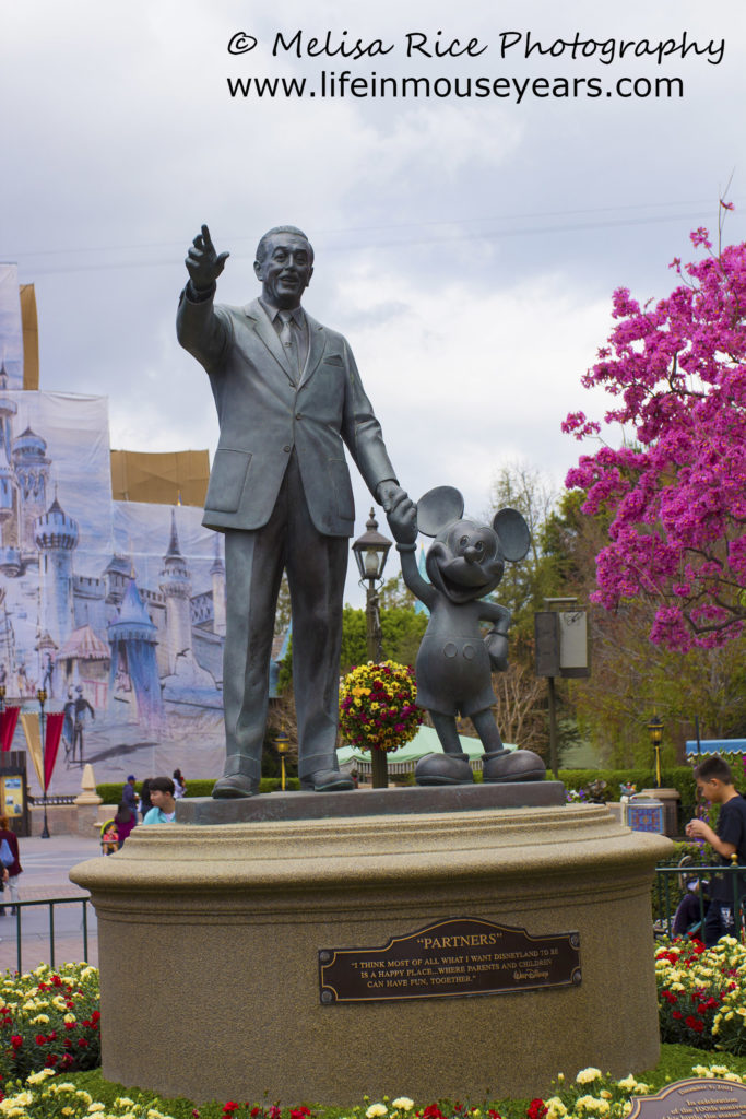 Partners statue with red and yellow flowers around the statue.