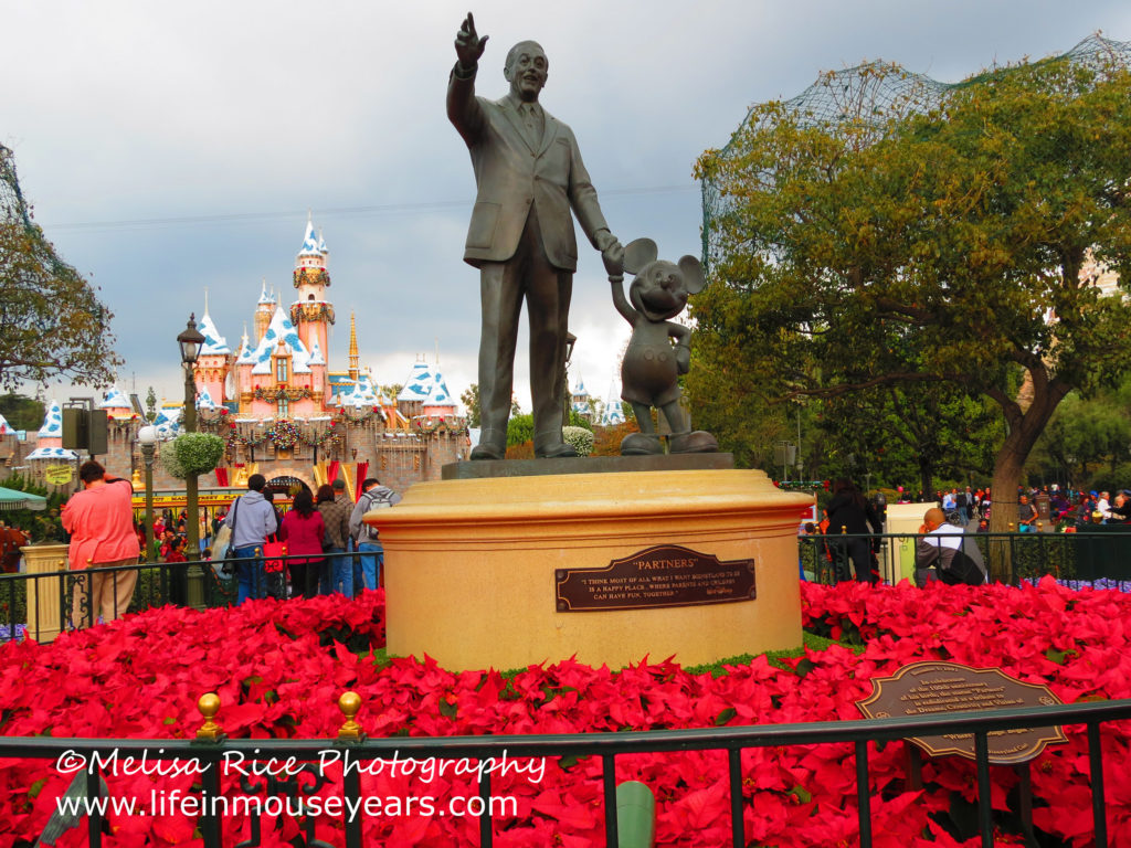 Partners statue in Disneyland from December with poinsettias surrounding the base.
